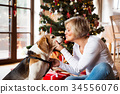 Senior woman with dog in front of Christmas tree 34556076