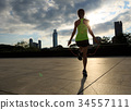 young fitness woman jumping rope on sunrise city building roof 34557111
