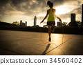 Young fitness woman jumping rope at sunrise city  34560402