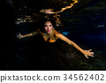 Mermaid swimming underwater in the deep blue sea 34562402