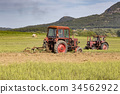 Old tractor working on the field 34562922