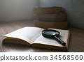 Magnification glass over a opened book in the room 34568569