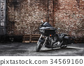 Modern black motorcycle stands against a brick 34569160
