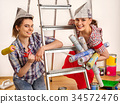 Repair home women holding painting tools roller 34572476