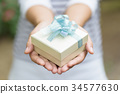 Silver gift box in hand for giving in holidays 34577630