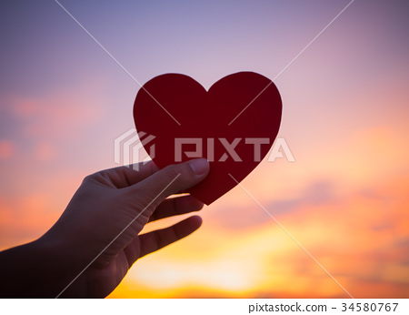 Closeup hand holding red heart during sunset
