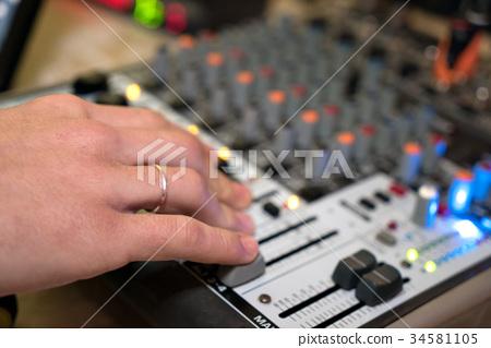 DJ working on a audiomixer at a nightclub 34581105