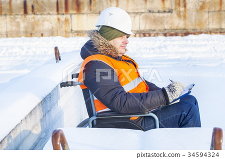Disabled worker on wheelchair writing 34594324