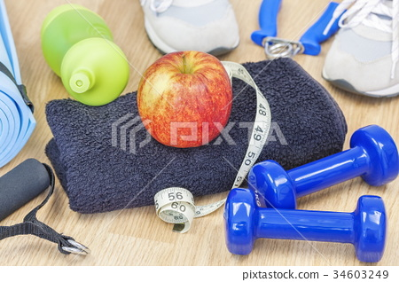 Apple on towel with fitness equipment and tape mea 34603249