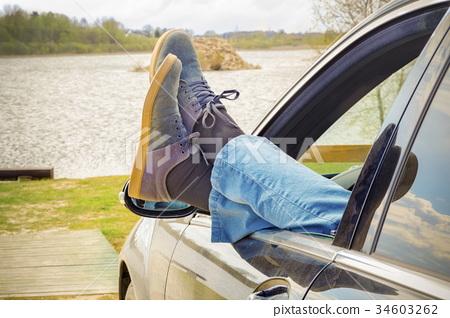 Man keep his legs through car window 34603262