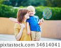 Little boy playing badminton with mom  34614041