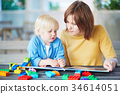 Young mother reading book to her son 34614051