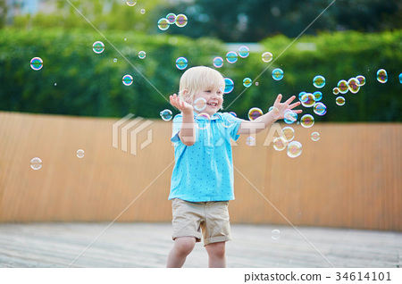 Little boy playing with bubbles outdoors 34614101