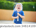 Little boy playing badminton on the playground 34614109