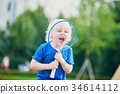 Little boy playing badminton on the playground 34614112