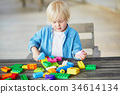 Little boy playing with colorful plastic construction blocks 34614134