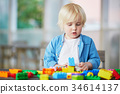 Little boy playing with colorful plastic construction blocks 34614137