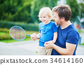 Little boy playing badminton with dad on the playground 34614160