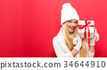 Young woman holding a Christmas gift 34644910