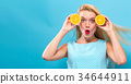 Happy young woman holding oranges  34644911