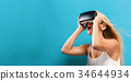 Young woman using virtual reality headset 34644934