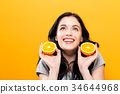 Happy young woman holding oranges  34644968