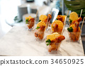fried chicken and potato chips in small cup 34650925