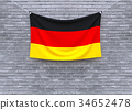 Germany flag hanging on brick wall.  34652478