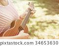 Anonymous woman playing ukulele 34653630