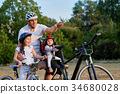 Cheerful family biking in park 34680028