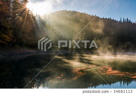 sun light in fog over the mountain lake Synevyr 34681113