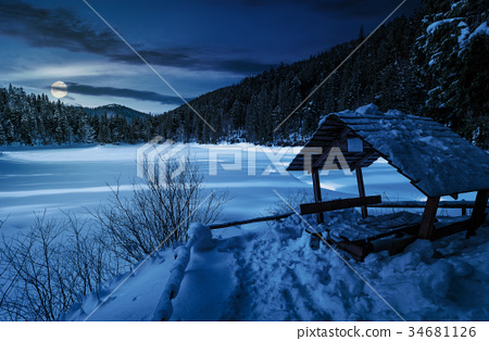wooden bower in snowy winter forest at night 34681126