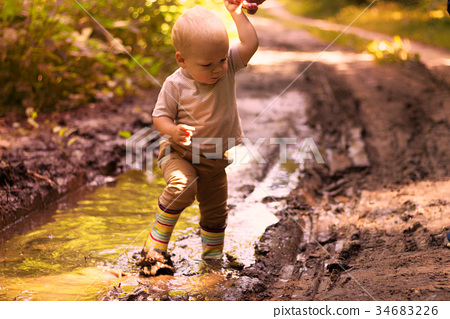 Funny baby boy having fun in a forest puddle 34683226