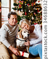 Senior couple in front of Christmas tree with 34688632