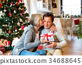 Senior couple in front of Christmas tree with 34688645