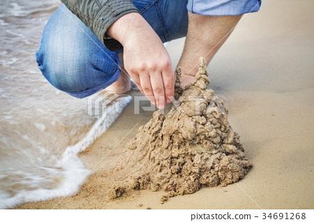 Man built sand castle near sea 34691268