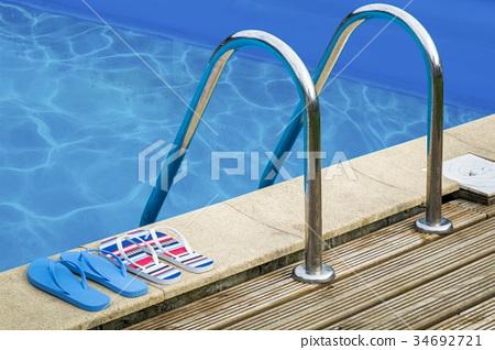 Flip flops and handles at swimming pool 34692721