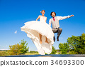 Bridal pair jumping outside on trampoline 34693300