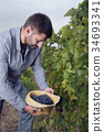 Man Holding Straw Hat Full Grapes Clusters 34693341