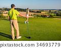 Man watching his partner striking the ball during 34693779