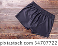 Black running shorts, wooden background. 34707722