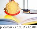 Golden medals and Graduation cap on book, graduate 34712308