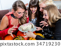 Four women wearing Halloween costumes while posing 34719230