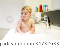 Cute adorable baby taking bath in washing sink and 34732633