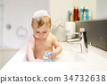 Cute adorable baby taking bath in washing sink and 34732638