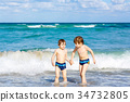 Two kid boys running on ocean beach in Florida 34732805