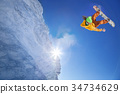 Snowboarder jumping against blue sky 34734629