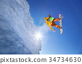 Snowboarder jumping against blue sky 34734630