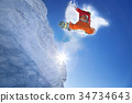 Snowboarder jumping against blue sky 34734643