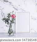 Blank frame and pink flowers over marble table 34736548